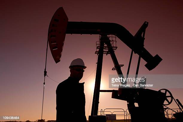 Silhouette of oil worker by pump jack on rig