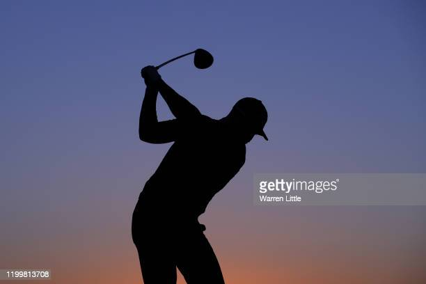 Silhouette of Oliver Fisher of England as he practices on the range as the sun rises during Day One of the Abu Dhabi HSBC Championship at Abu Dhabi...