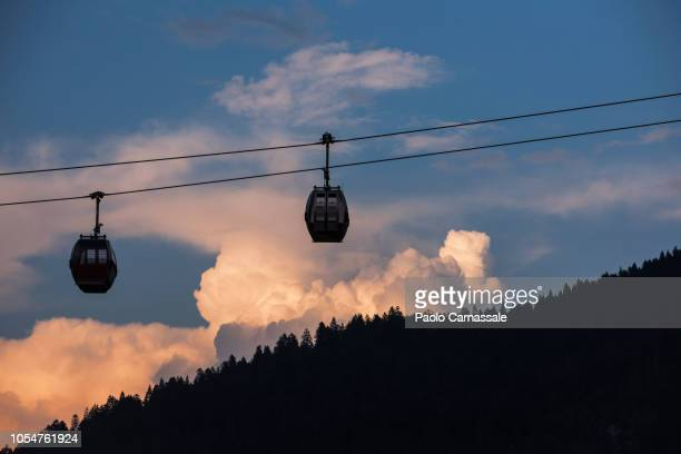 silhouette of overhead cable car against the sky at sunset - overhead cable car stock pictures, royalty-free photos & images