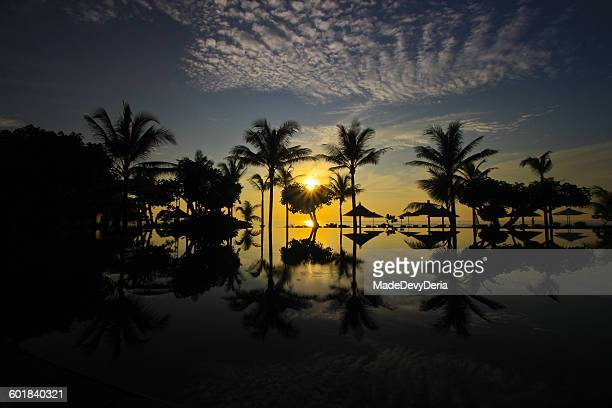 Silhouette of palm trees, parasols and swimming pool at sunrise, Bali, Indonesia