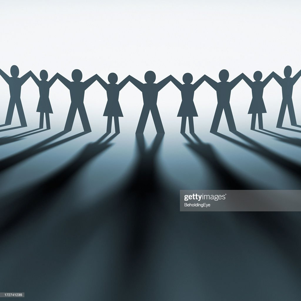 silhouette of paper cutout of people holding hands stock photo