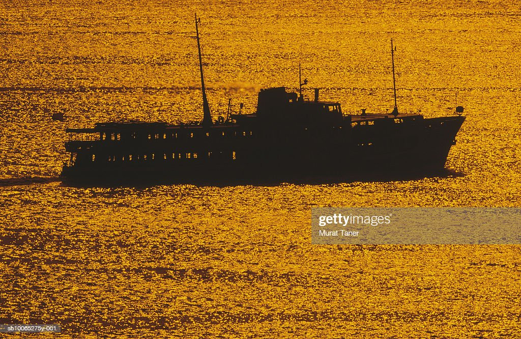Silhouette of passanger ferry in sea at sunset : Foto stock