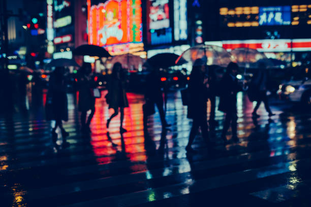 Silhouette of pedestrians crossing street against glowing neon lights in the city on a rainy night.