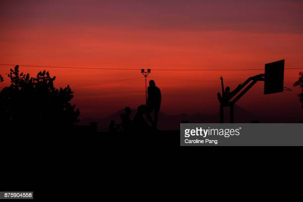 Silhouette of people against the warm red sky of sunset in Ende, Flores Indonesia.