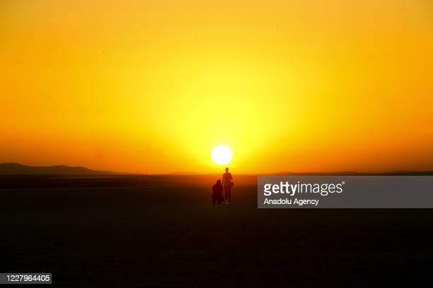 Silhouette of people are seen during the sunset in Lake Salt in Ankara, Turkey on August 07, 2020. Lake Salt is one of the most important wetlands...