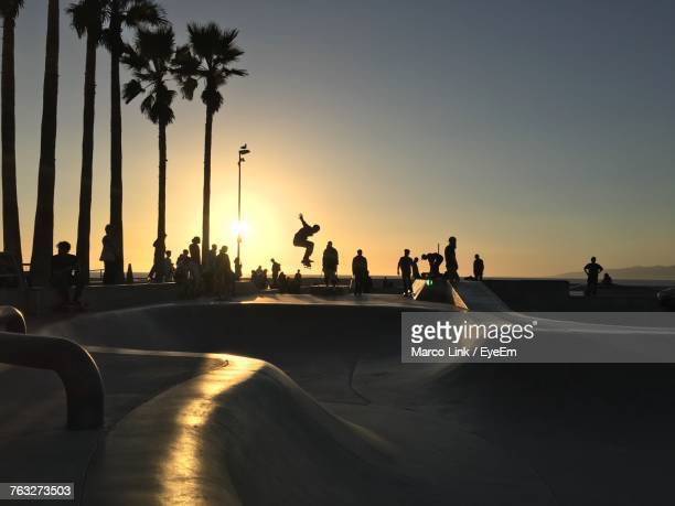silhouette of people at skateboard park against sky during sunset - san fernando california stock photos and pictures
