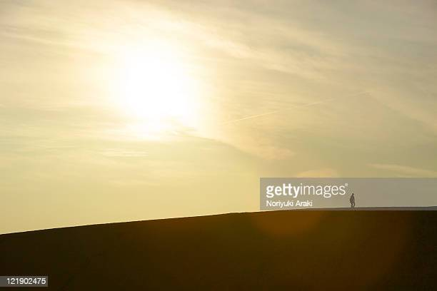 Silhouette of people at sunset on dunes