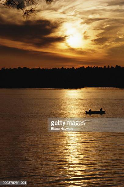 Silhouette of people boating on lake