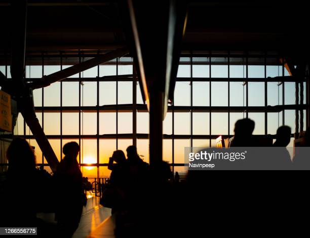 silhouette of people busily walking through airport terminals as the sunset, uk - airport stock pictures, royalty-free photos & images