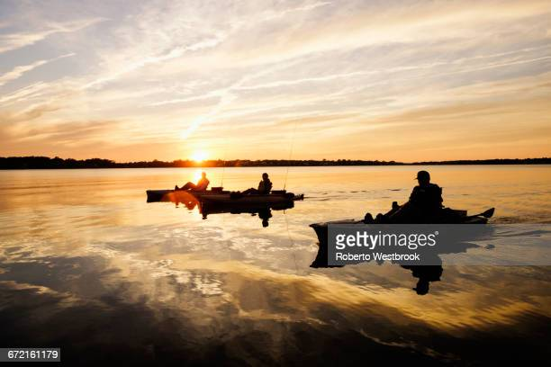 silhouette of people fly fishing in kayaks on river - virginia beach stock photos and pictures