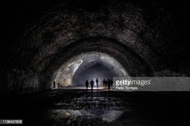 Silhouette of people inside abandoned underground tunnel