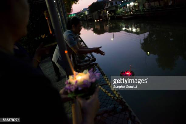 Silhouette of people lower their krathong on Saen Saep canal in Bangkok, Thailand