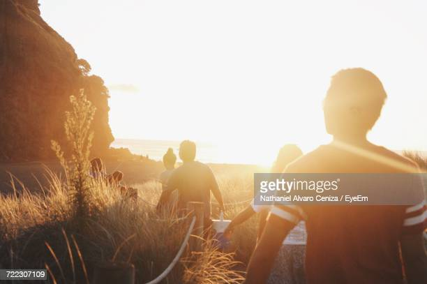 silhouette of people on beach at sunset - new zealand stock pictures, royalty-free photos & images