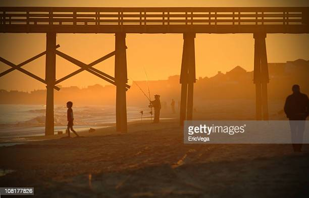 Silhouette of People on Beach Below Pier at Sunset
