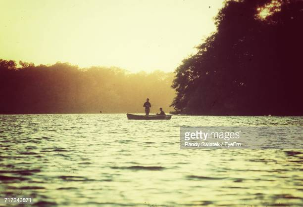 silhouette of people on boat in river - swiatek stock pictures, royalty-free photos & images