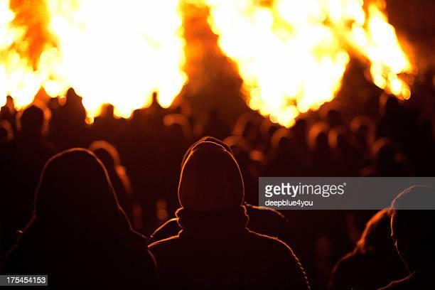 Silhouette von Menschen am Feuer bei Nacht