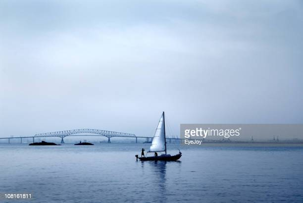 Silhouette of People on Sailboat with Bridge in Background