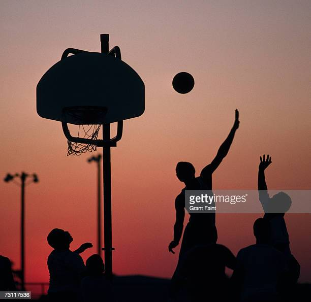 Silhouette of people playing basketball at sunset