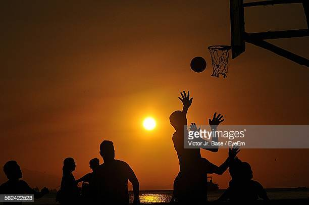 Silhouette Of People Playing Basketball, Yellow Sun In Sky