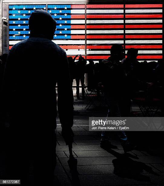 Silhouette Of People Standing In Front Of American Flag