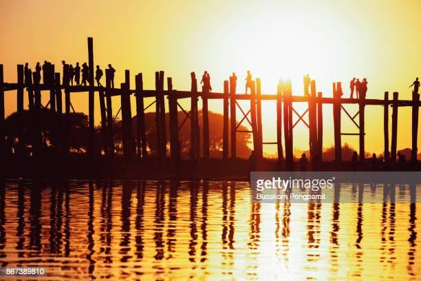 silhouette of people traveling across the U Bein Bridge in the evening. U bein bridge