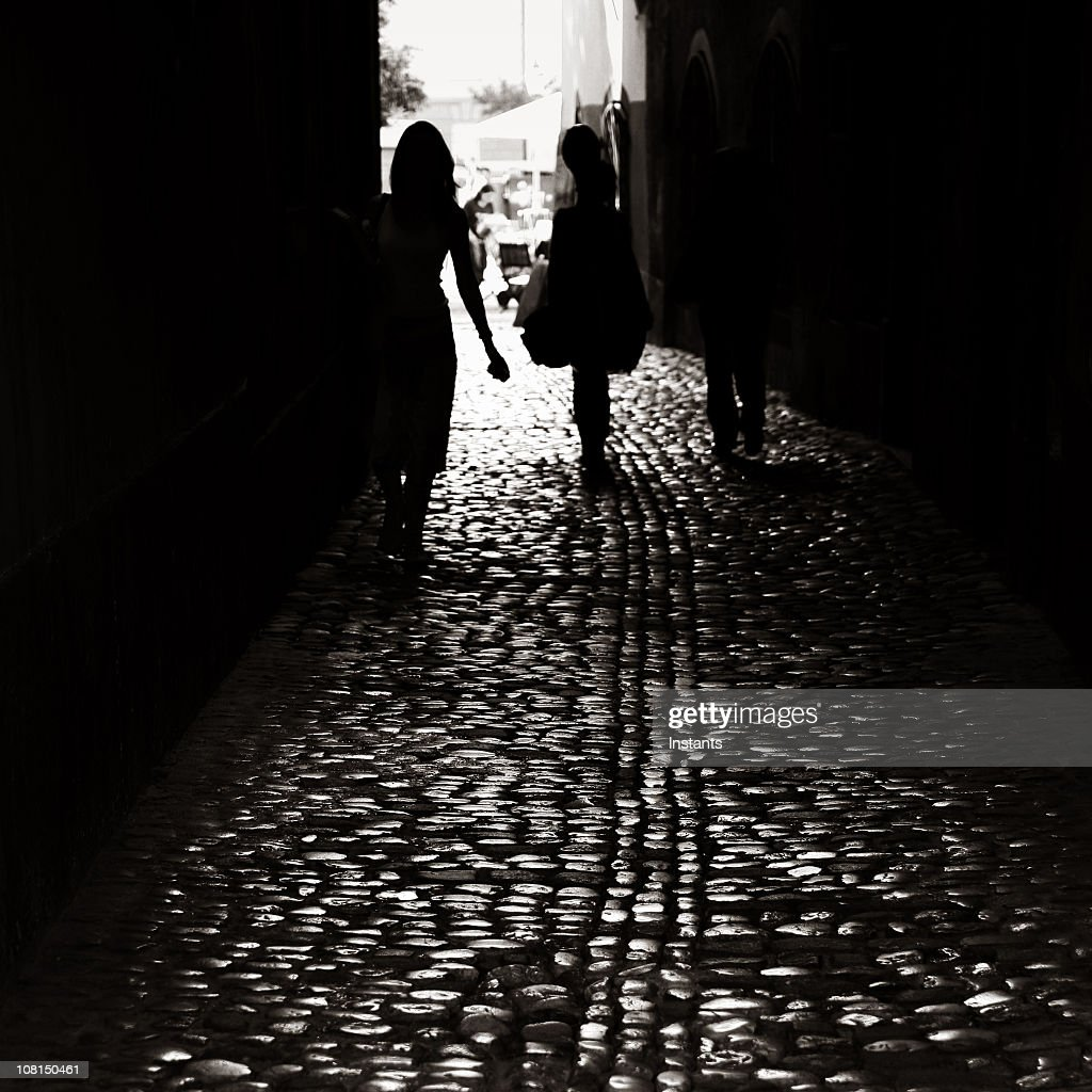 Silhouette of people walking down dark cobblestone alley : Stock Photo
