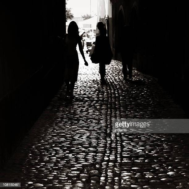 silhouette of people walking down dark cobblestone alley - black alley stock photos and pictures