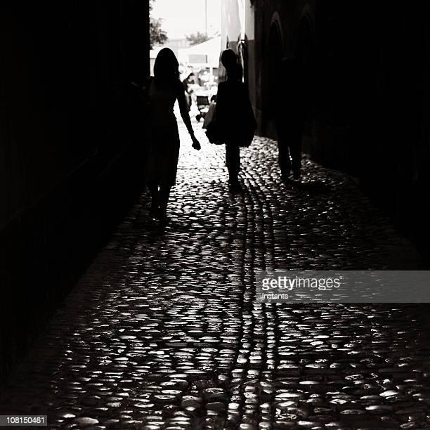 Silhouette of people walking down dark cobblestone alley