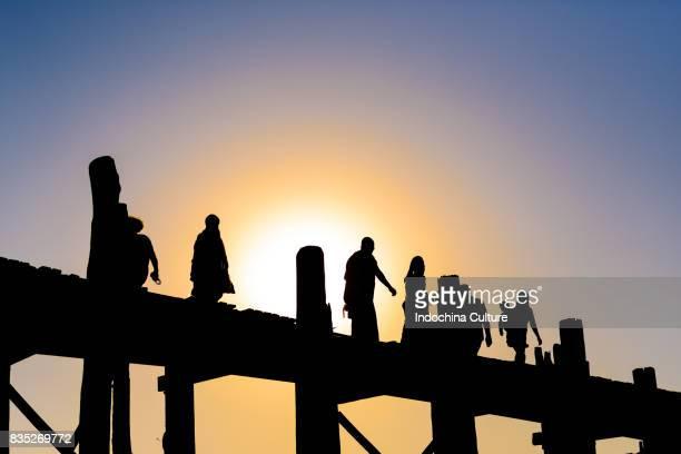 Silhouette of people walking on Ubein bridge, world longest wooden bridge, Mandalay, Myanmar