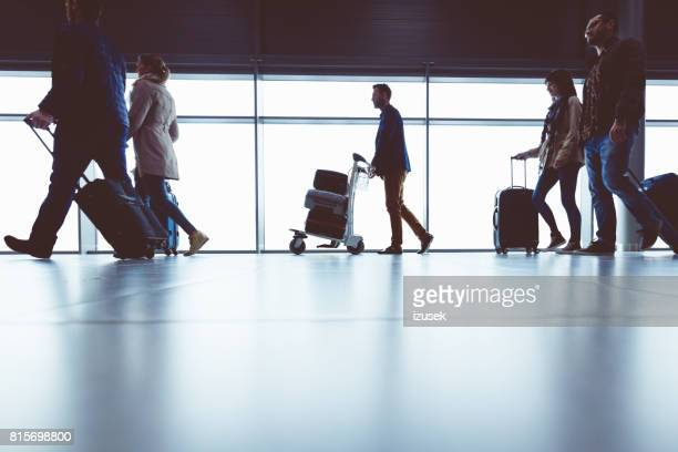 Silhouette of people walking with luggage in airport terminal
