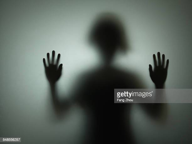 Silhouette of person behind glass