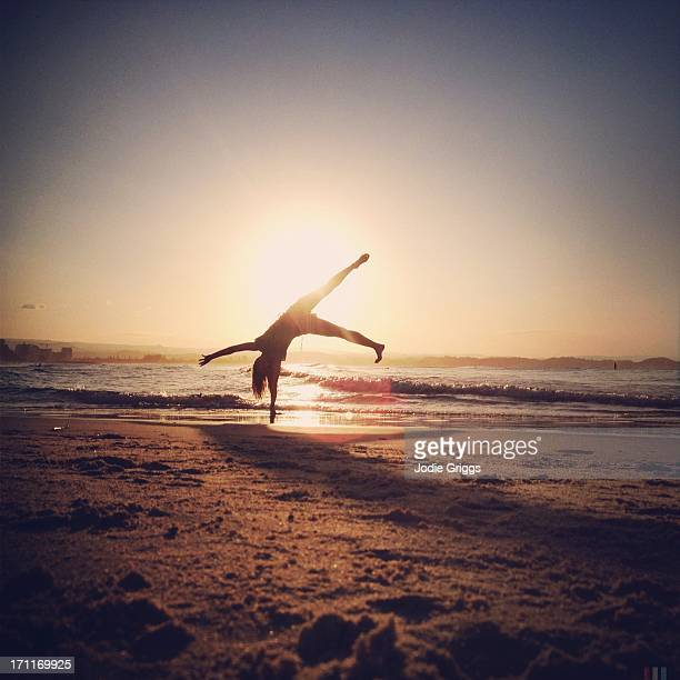 Silhouette of person cartwheeling at beach sunset
