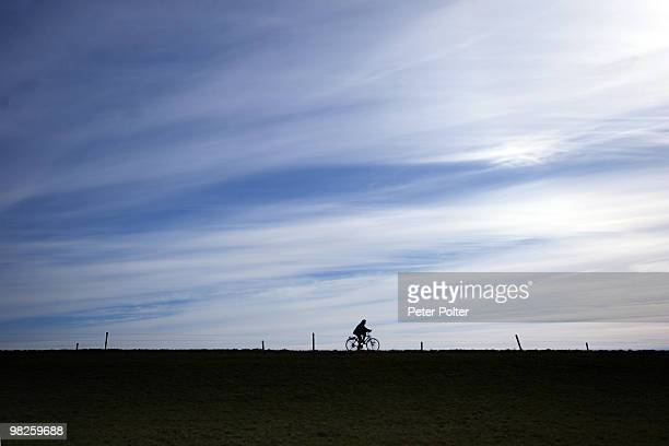 Silhouette of person cycling on dike