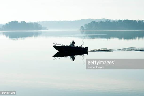 Silhouette of person fishing in lake