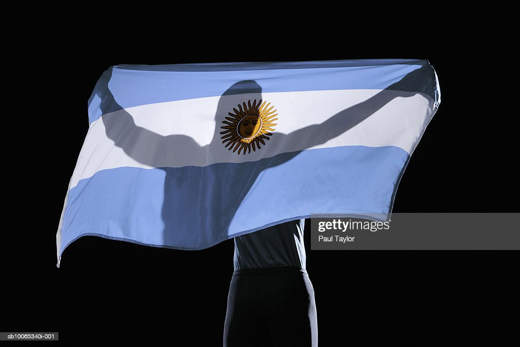 Silhouette of person holding flag of Argentina on black background : Foto stock