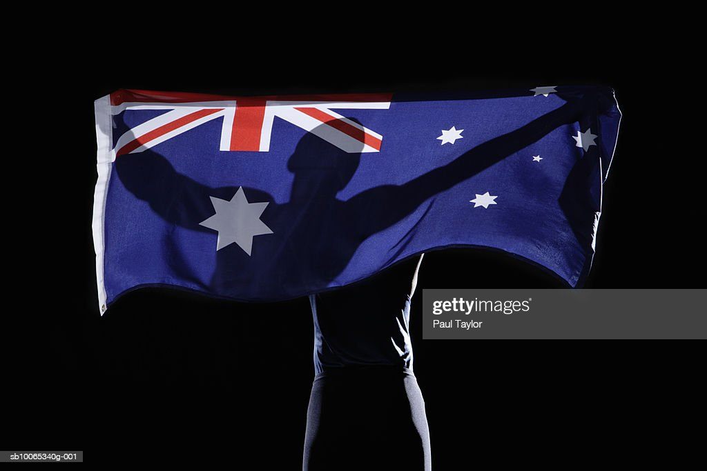 Silhouette of person holding flag of Australia on black background : Foto stock