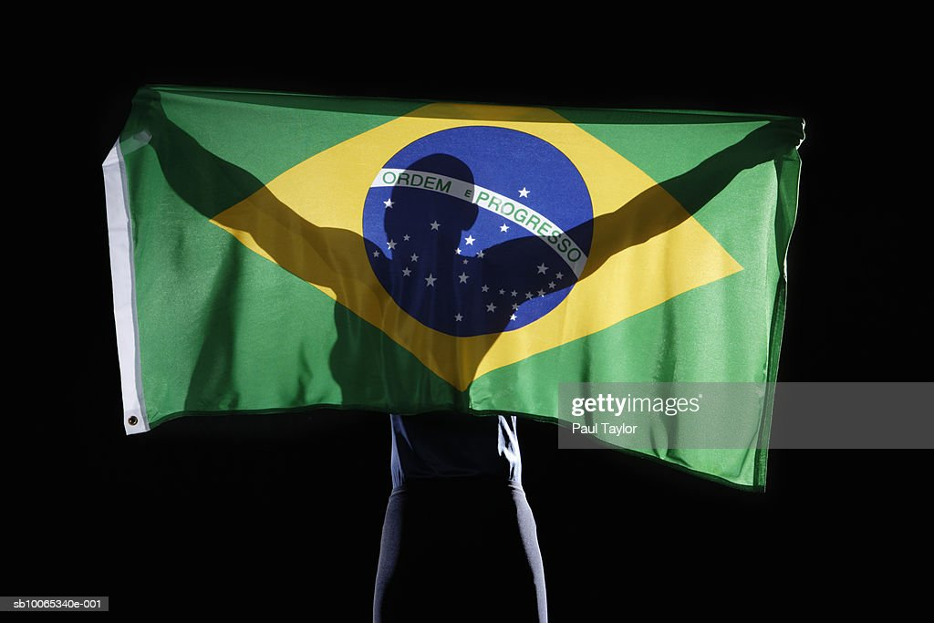Silhouette of person holding flag of Brazil on black background : Foto stock