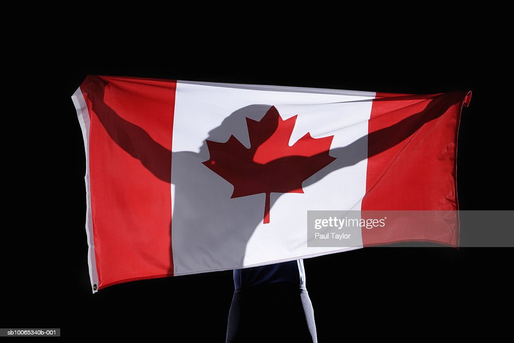Silhouette of person holding flag of Canada on black background : Foto stock