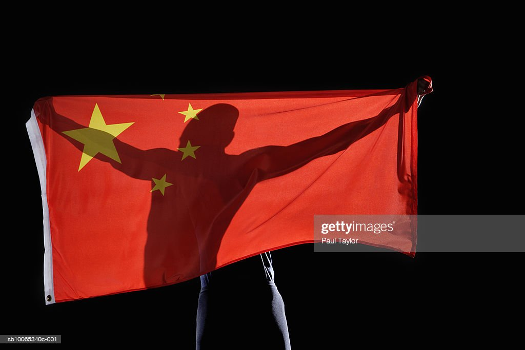 Silhouette of person holding flag of China on black background : Foto stock