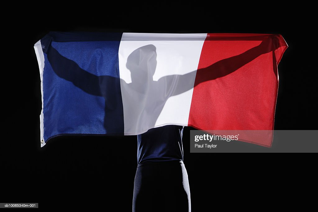 Silhouette of person holding flag of France on black background : Foto stock