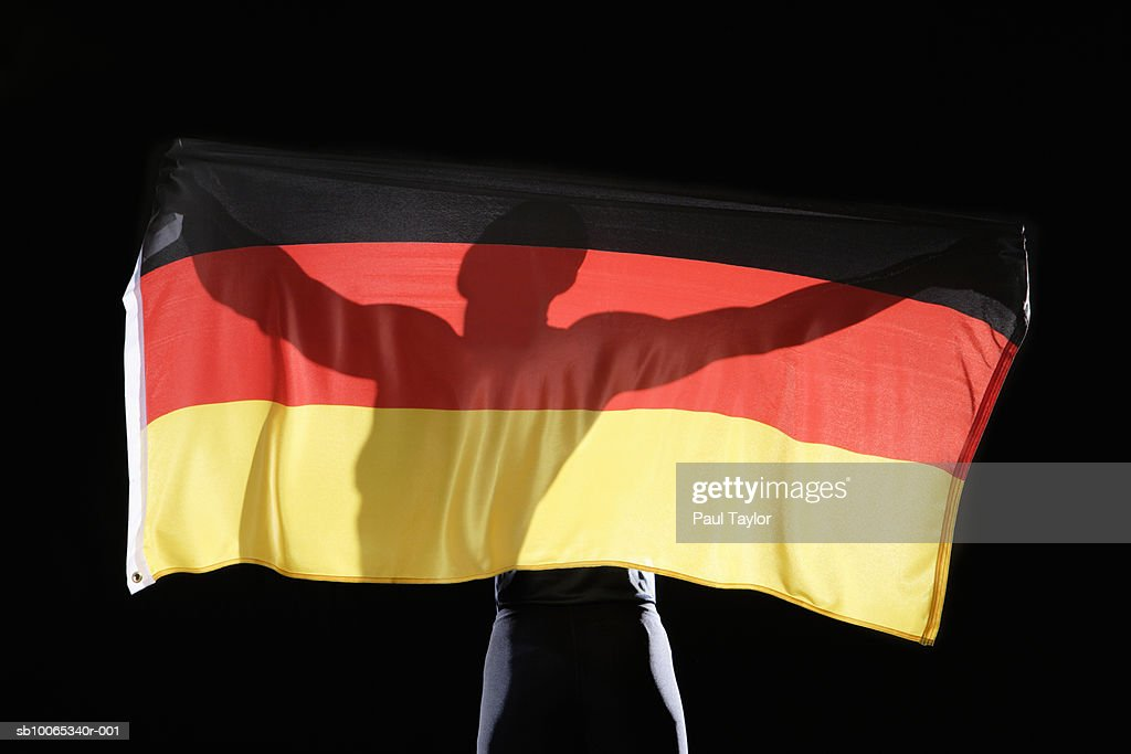 Silhouette of person holding flag of Germany on black background : Foto stock