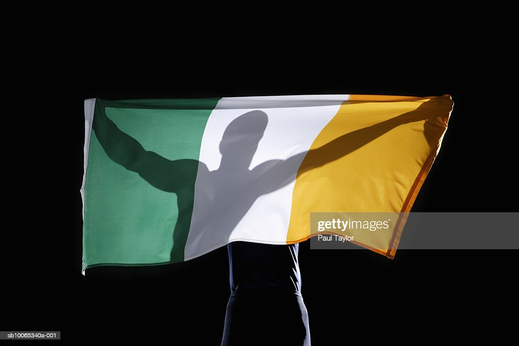 Silhouette of person holding flag of Ireland on black background : Foto stock