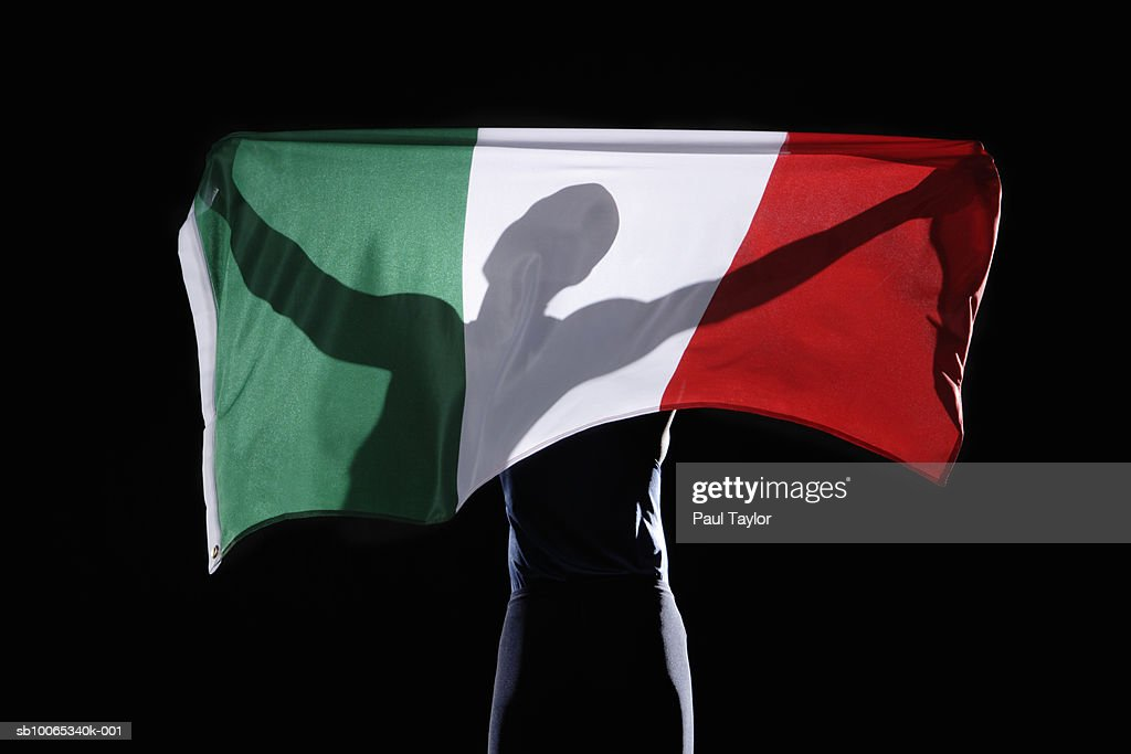 Silhouette of person holding flag of Italy on black background : Foto stock