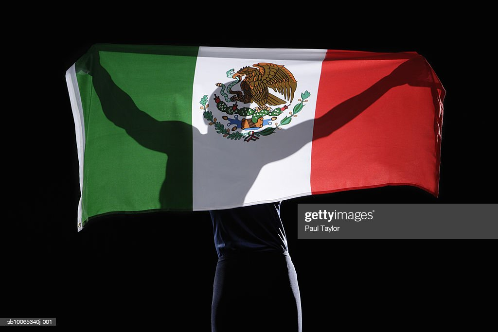 Silhouette of person holding flag of Mexico on black background : Foto stock