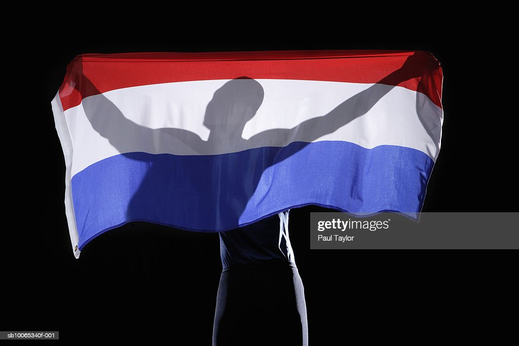 Silhouette of person holding flag of Netherlands on black background : Foto stock
