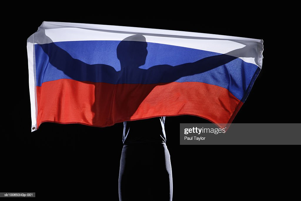 Silhouette of person holding flag of Russian Federation on black background : Foto stock