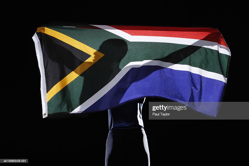 Silhouette of person holding flag of South Africa on black background : Foto stock
