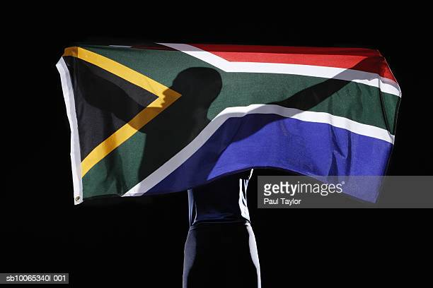 silhouette of person holding flag of south africa on black background - south african flag stock photos and pictures