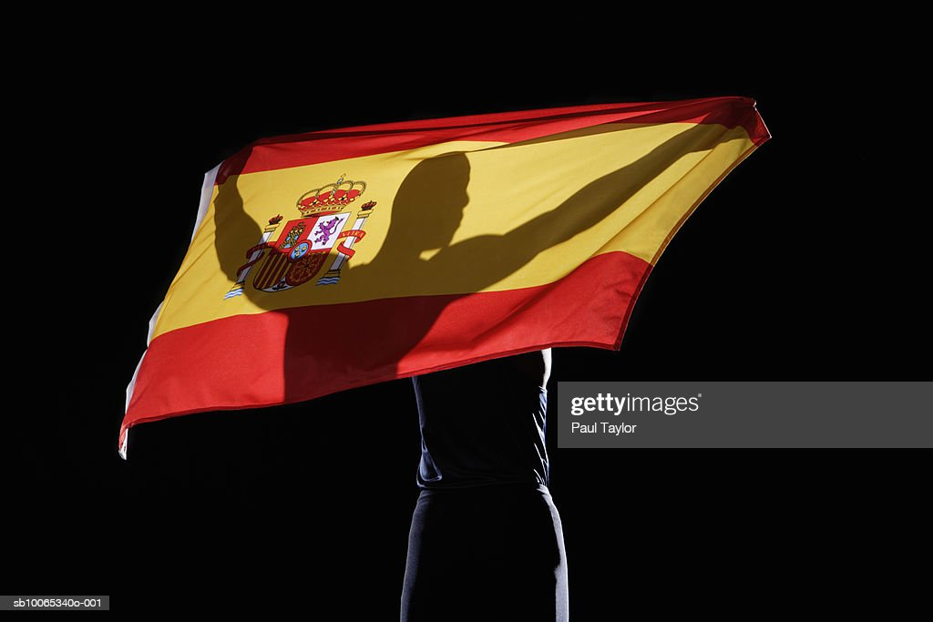 Silhouette of person holding flag of Spain on black background : Foto stock