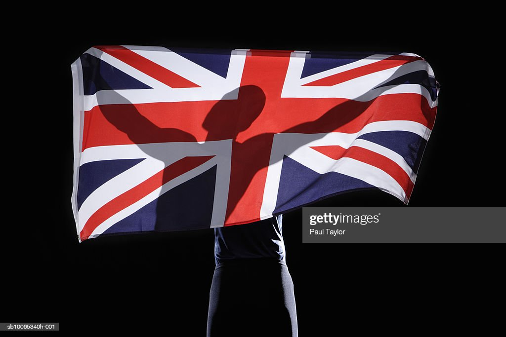 Silhouette of person holding flag of United Kingdom on black background : Foto stock